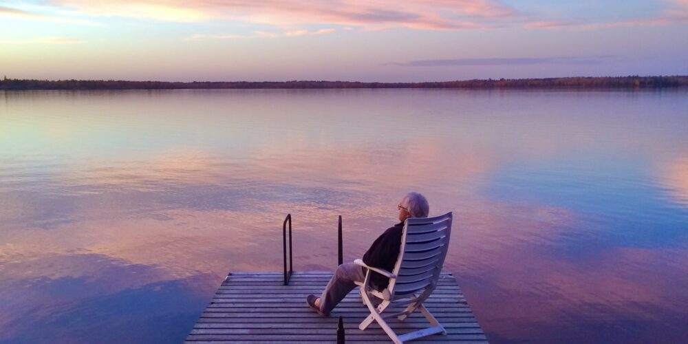 Man,alone, sitting on dock at sunset.